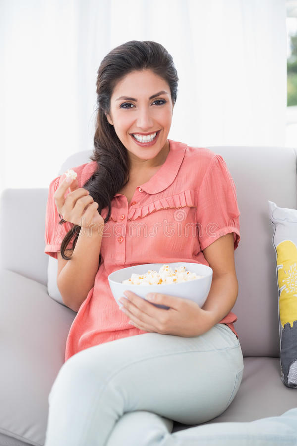 Assento moreno alegre em seu sofá que come a bacia de pipoca fotografia de stock