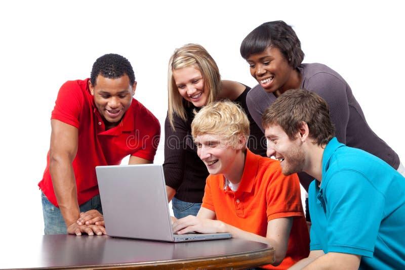 Assento Multi-racial dos estudantes universitários um computador fotos de stock royalty free