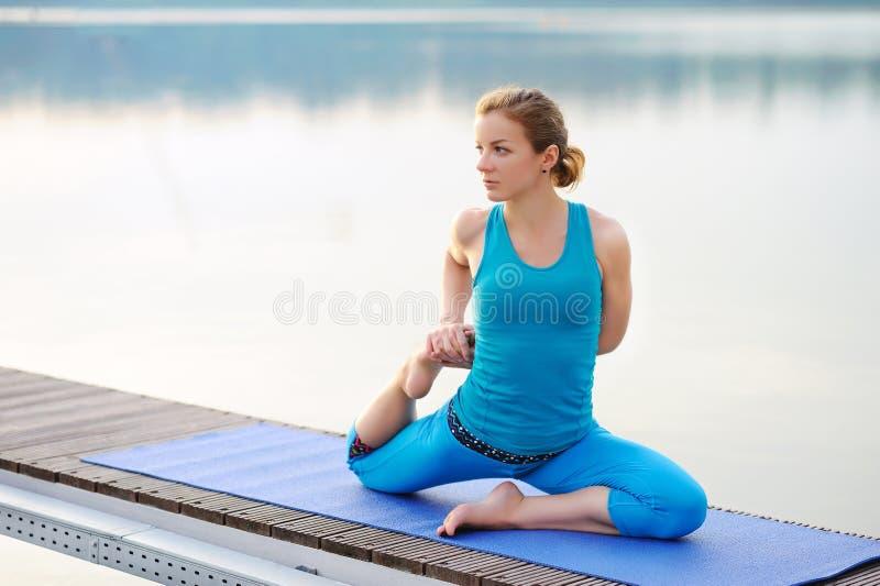 Assento na menina da ioga do banco de rio que estica e que prepara-se para foto de stock