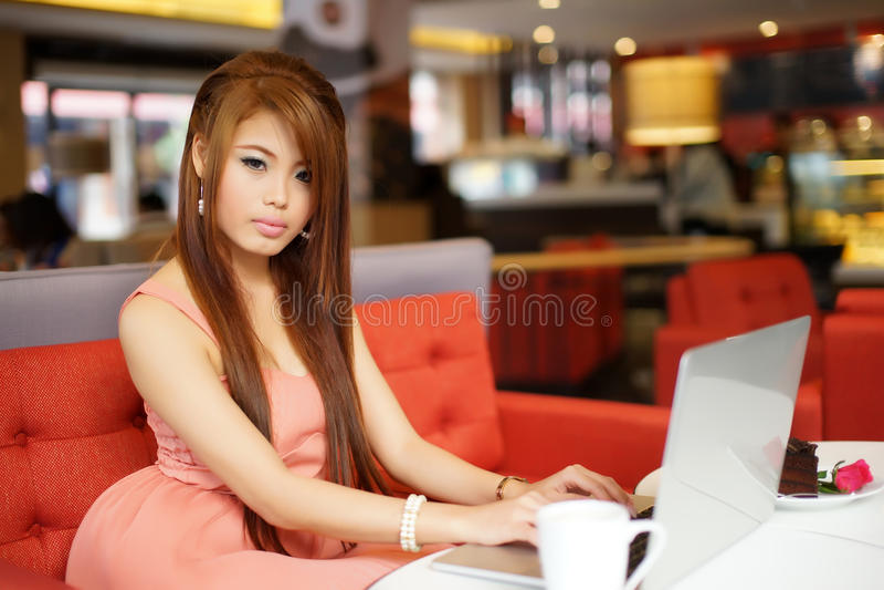 Assento novo da mulher de negócio mim café com seu portátil foto de stock royalty free