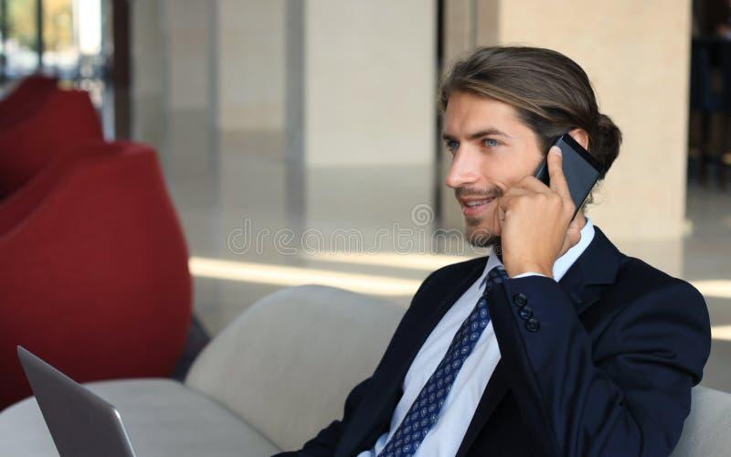 Assento novo do homem de negócios relaxado no sofá na entrada do hotel que faz um telefonema, esperando alguém imagens de stock