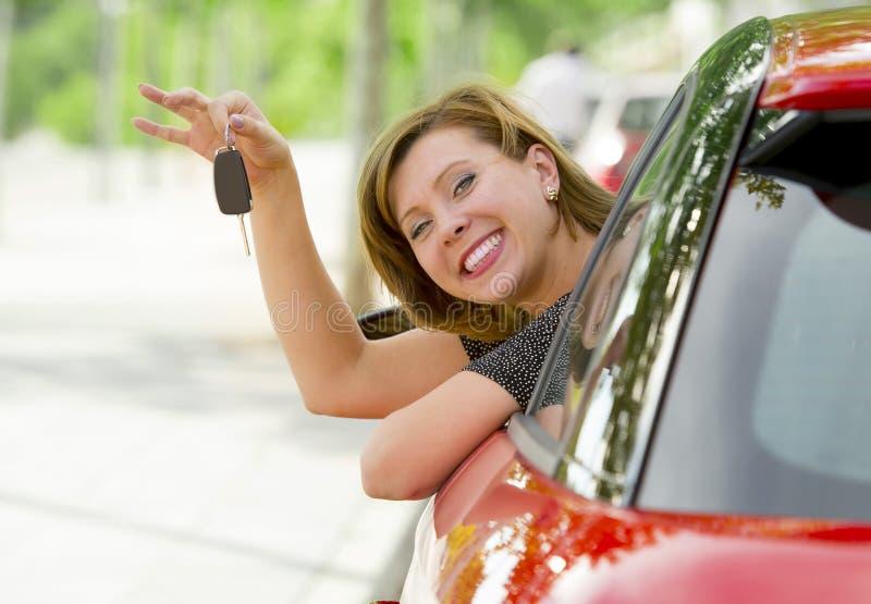 Assento orgulhoso de sorriso da mulher atrativa feliz nova no banco do condutor que realiza e que mostra a chave do carro na comp imagem de stock royalty free
