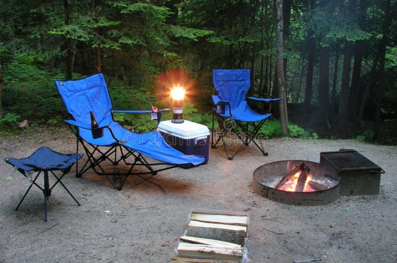 Assento pelo incêndio em um campsite imagem de stock royalty free