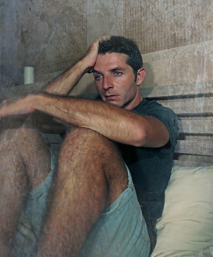 Assento pensativo e pensativo atrativo novo do homem triste e desesperado no sentimento de sofrimento da depressão do quarto da c foto de stock