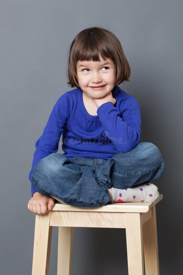 Assento pré-escolar insolente da criança, relaxando com pés cruzados foto de stock royalty free