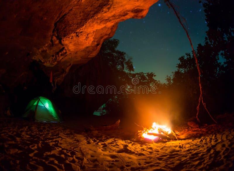 Assento romântico dos pares do carro de acampamento da barraca pelo campo da noite da fogueira fotografia de stock royalty free