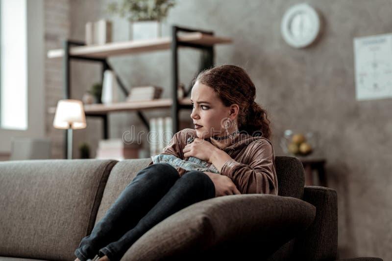 Assento só e infeliz do sentimento do adolescente no sofá em casa fotos de stock
