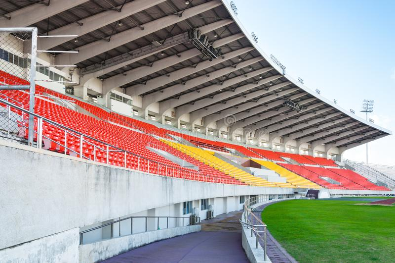 Assentos alaranjados e amarelos vazios no estádio, passagem das fileiras do assento em um estádio de futebol fotografia de stock royalty free