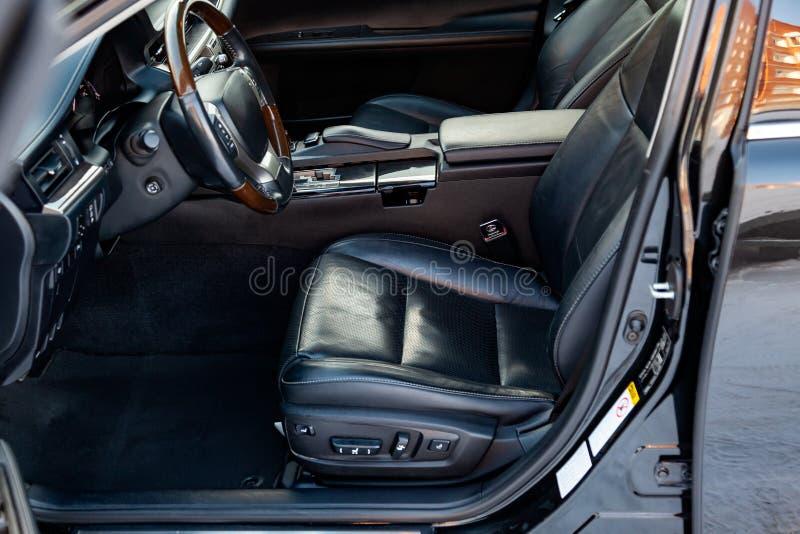 Assentos dianteiros confortáveis dentro do carro: o motorista e o passageiro, amarrados com couro preto genuíno, design de interi imagem de stock royalty free