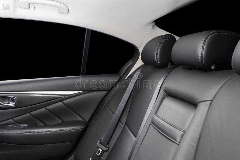 Assentos do passageiro traseiros no carro luxuoso moderno, vista frontal Couro perfurado preto com costura branca Detalhe do carr imagem de stock royalty free