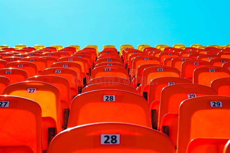 Assentos plásticos vazios brilhantes vermelhos na plataforma dos esportes do estádio fotografia de stock
