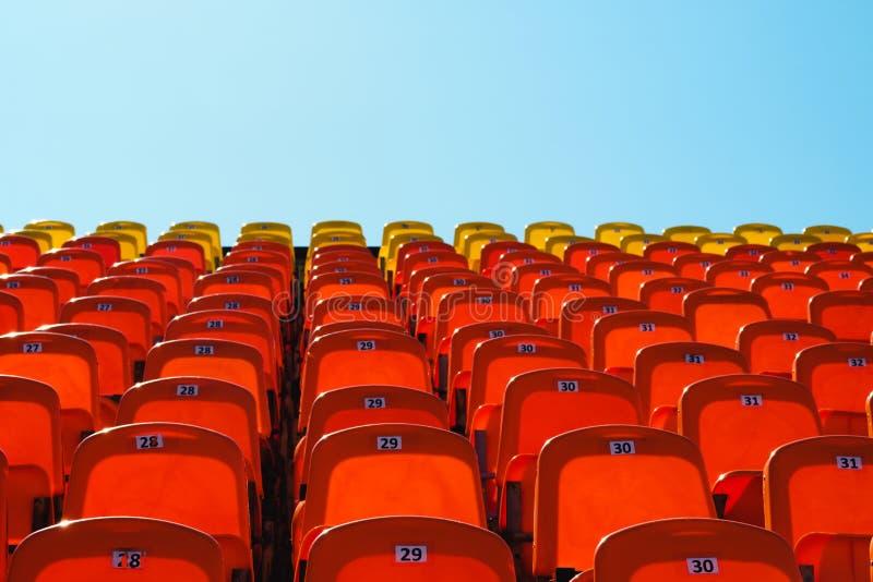 Assentos plásticos vermelhos contra um céu azul brilhante imagem de stock royalty free