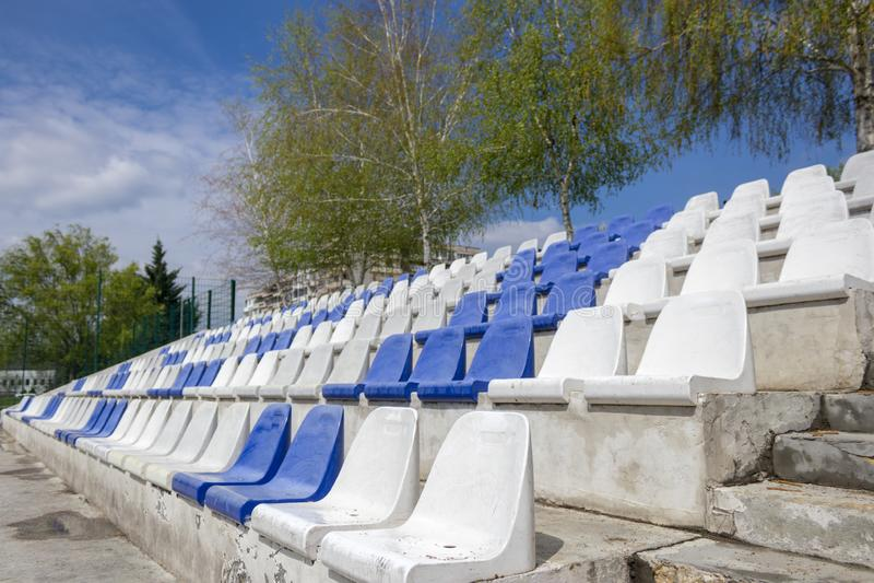 Assentos vazios plásticos brancos e azuis do estádio na arena fotos de stock