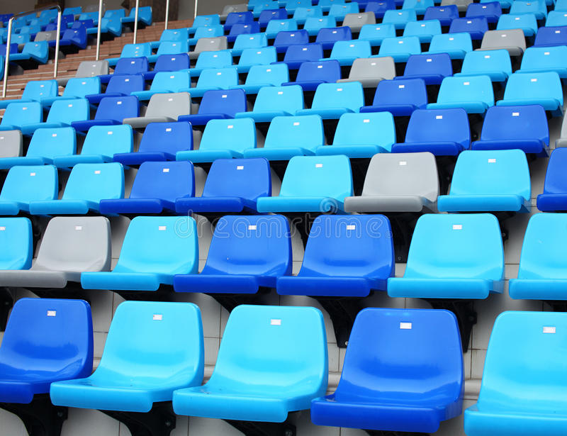Assentos velhos plásticos azuis do estádio em passos concretos fotos de stock