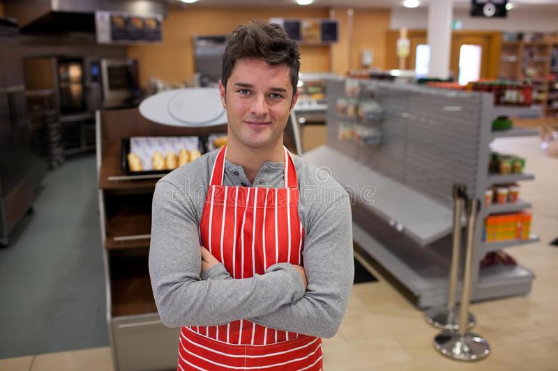 Assertive cook smiling at the camera. In front of his bakery royalty free stock photography