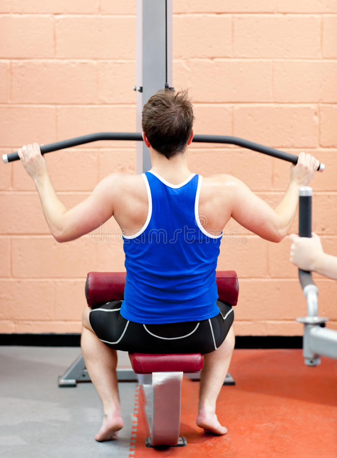 Assertive male athlete practicing body-building stock photo