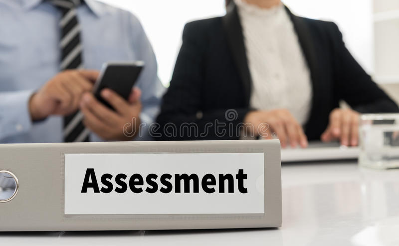Assessments. Assessment file on desk with executives and auditors in office stock photography