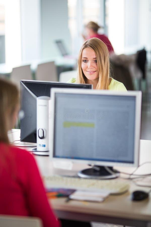 Assez, étudiante regardant un écran d'ordinateur de bureau photo libre de droits