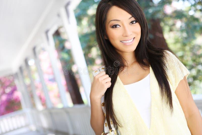 Assez Asiatique à la maison sur le porche photo stock
