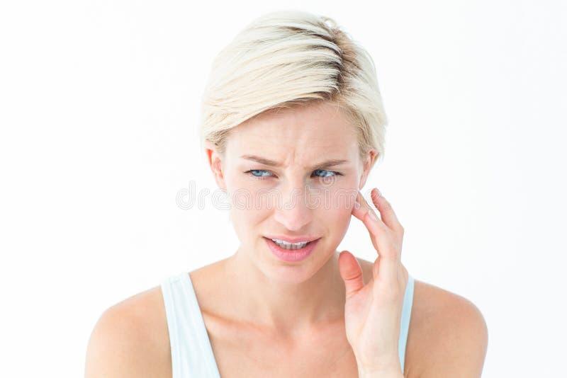 Assez blond avec douleur de dent images stock