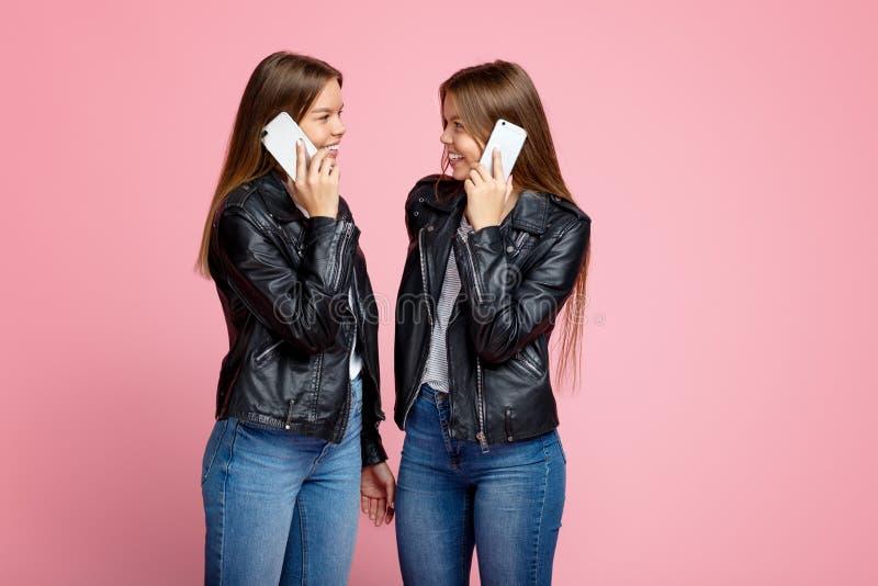Assez deux jeunes soeurs jumelles avec l'entretien lumineux de sourire sur le smartphone au-dessus du fond rose images stock