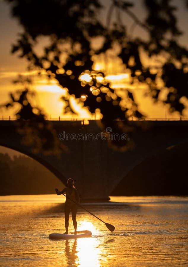 Assez, embarquement de palette de jeune femme sur un beau lac dans la lumière chaude de fin de l'après-midi photo stock