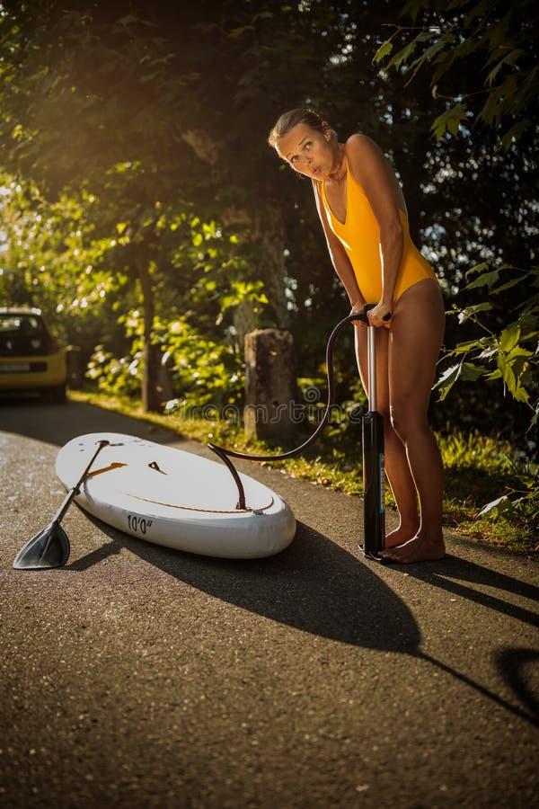 Assez, embarquement de palette de jeune femme sur un beau lac dans la lumière chaude de fin de l'après-midi photographie stock libre de droits
