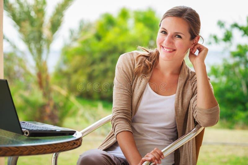 Assez, jeune femme à l'aide d'un ordinateur portable à la maison image libre de droits