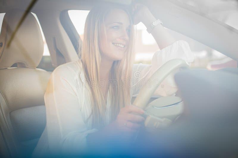 Assez, jeune femme conduisant une voiture image stock