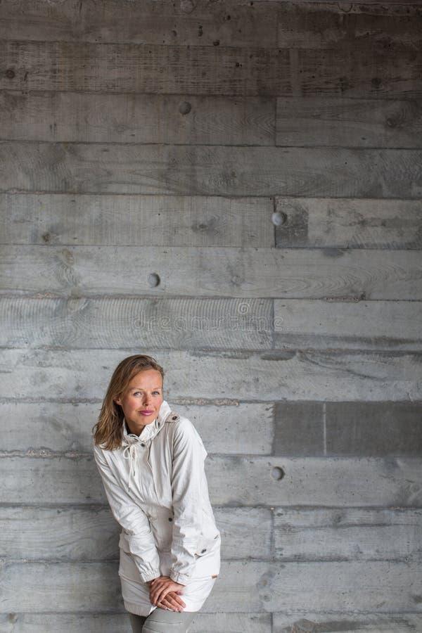 Assez, jeune femme devant un mur en béton image stock