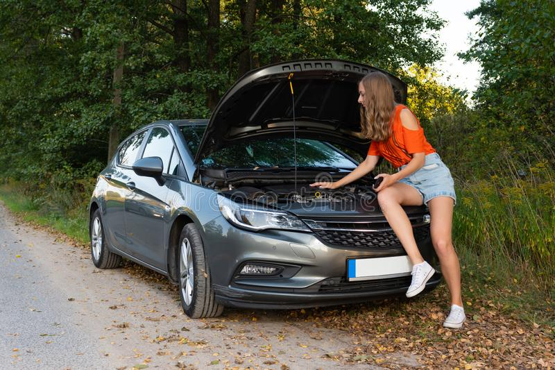 Assez, jeune femme par le bord de la route après que sa voiture ait été en panne - image photographie stock