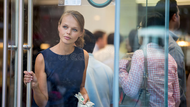 Assez, jeune femme quittant un magasin/restaurant images stock
