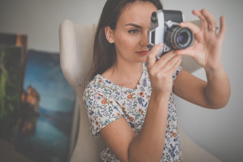 Assez, jeune photographe féminin dans son studio prenant des photos avec une caméra de film de cru photos stock