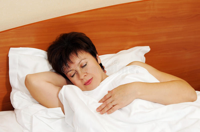 Assez la femme âgée par milieu dort solidement dans un lit image stock