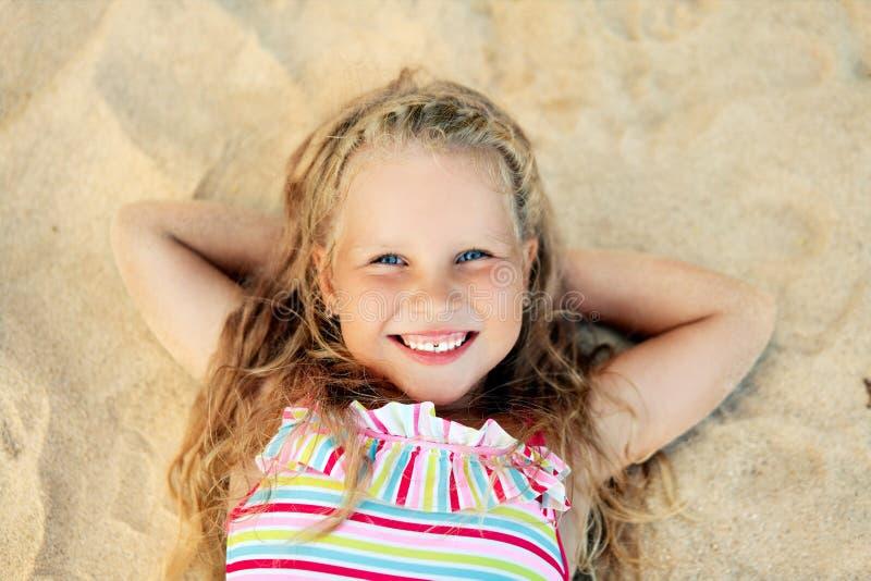Assez peu de portrait blond de fille se trouvant sur la plage sablonneuse pendant des vacances d'été images libres de droits