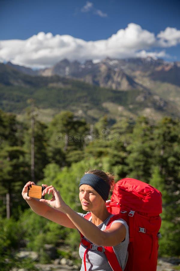 Assez, randonneur de jeune femme prenant une photo de selfie images libres de droits