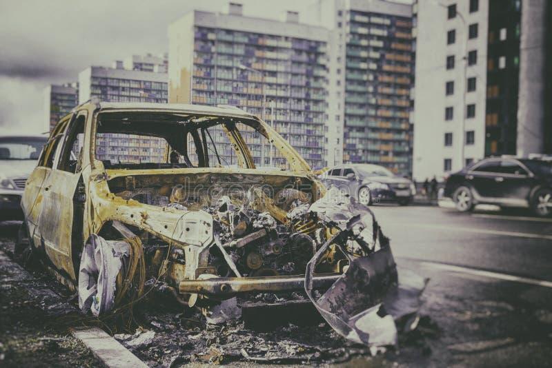 Assicurazione auto contro fuoco, automobile bruciata contro lo sfondo della città immagini stock