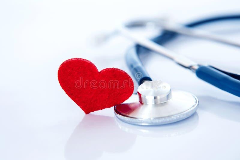 Assicurazione malattia e concetto medico della malattia cardiaca di sanità, una forma rossa del cuore con lo stetoscopio su fondo immagini stock