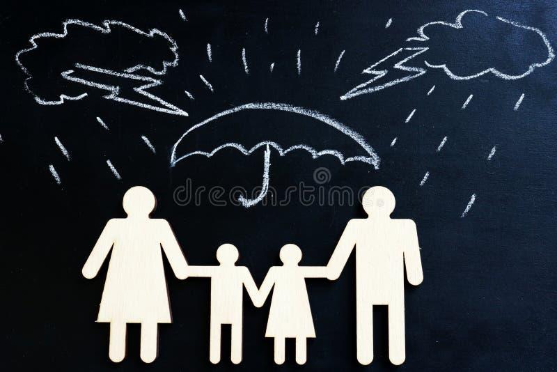 Assicurazione sulla vita Figure tirate della famiglia e della pioggia sotto l'ombrello immagine stock