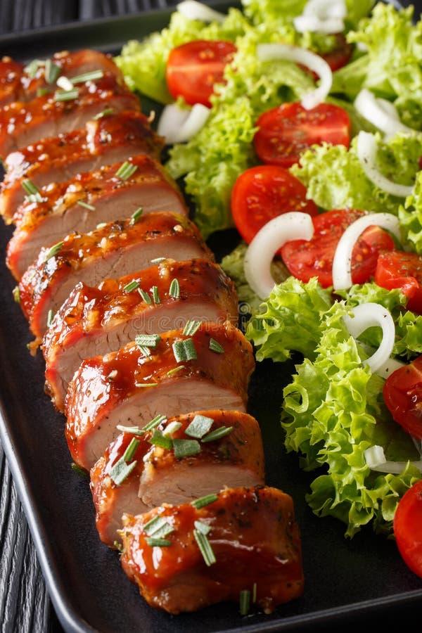 Assiette de porc cuite à la tendresse dans une sauce à l'ail au miel, servie avec une salade de légumes sur une assiette vertical photo stock
