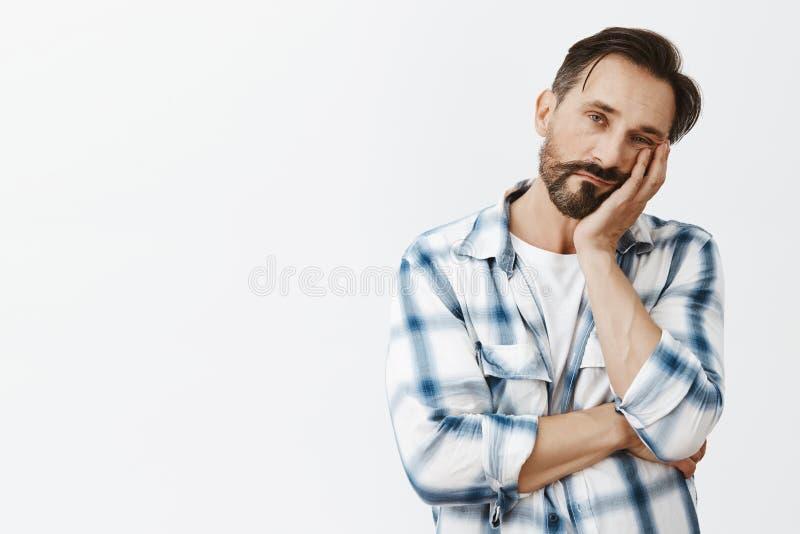 Assim furando Homem adulto bonito indiferente com barba e cabelo escuro, cara de inclinação na palma e olhar com cansado descuida fotografia de stock