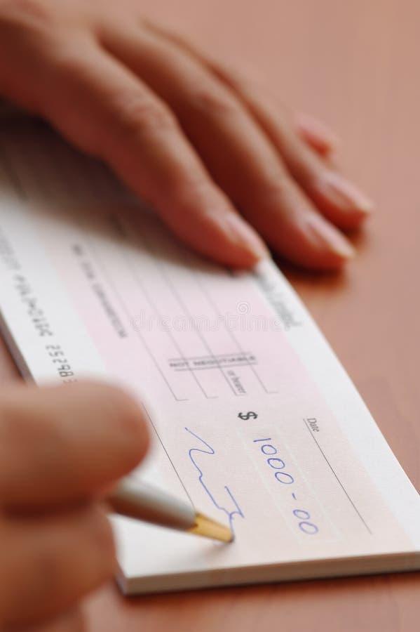 Assinando um cheque do dinheiro foto de stock