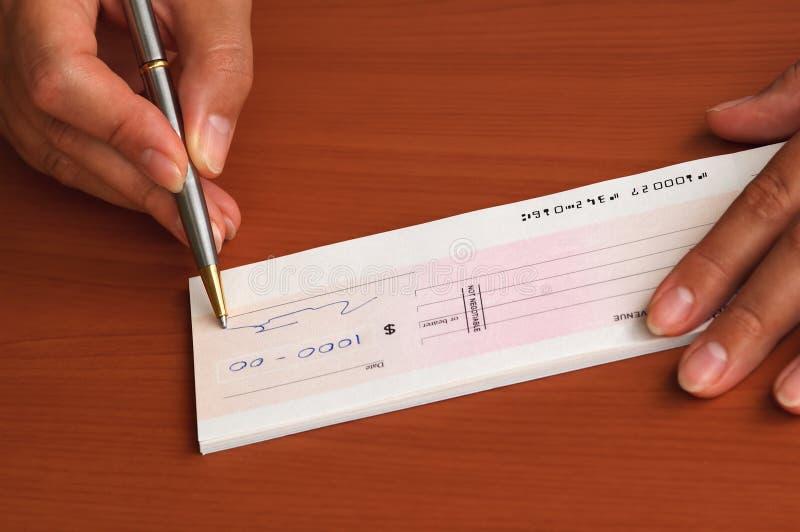 Assinando um cheque do dinheiro fotos de stock