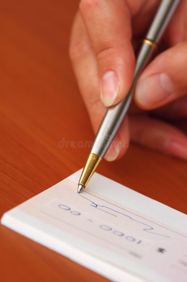 Assinando um cheque do dinheiro imagens de stock royalty free