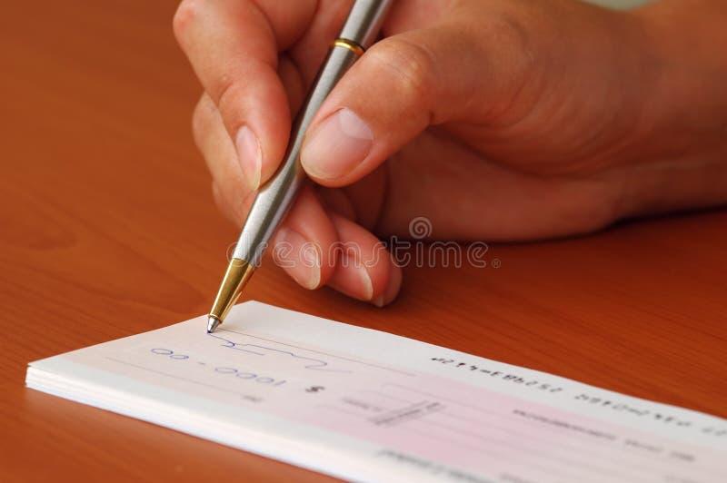 Assinando um cheque do dinheiro imagens de stock