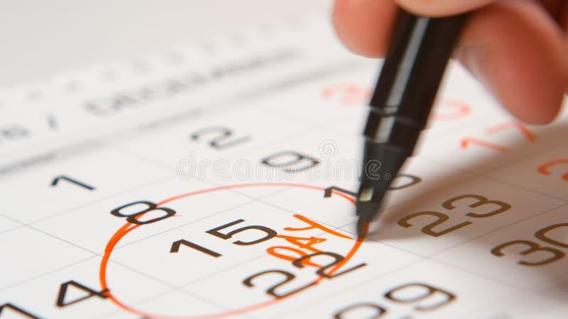 Assinando um dia de pagamento em um calendário pela pena vermelha imagens de stock royalty free