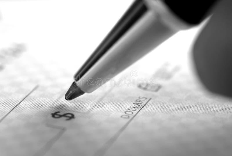 Assinando uma verificação para finanças pessoais fotografia de stock