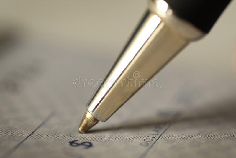 Assinando uma verificação para finanças pessoais foto de stock