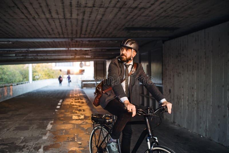 Assinante do homem de negócios do moderno com a bicicleta elétrica que viaja ao trabalho na cidade fotografia de stock