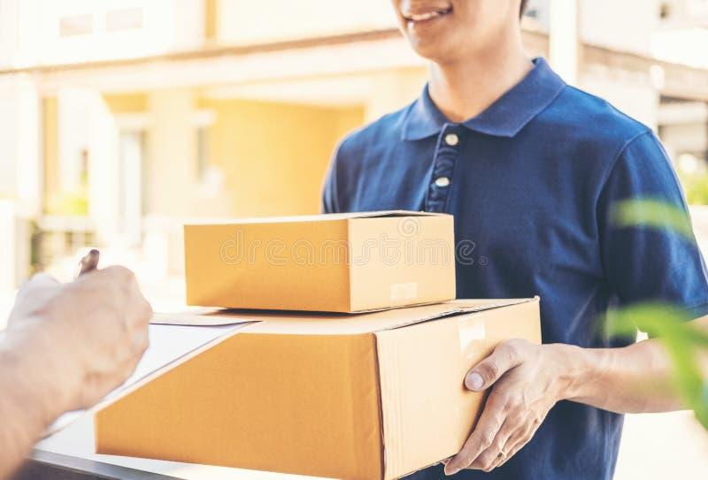 Assinatura do homem do cliente na prancheta para receber em casa o pacote do homem de entrega profissional foto de stock